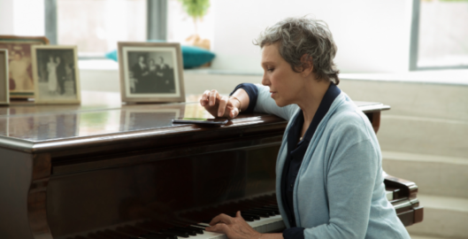 Woman playing piano with Widex Evoke machine learning hearing aids
