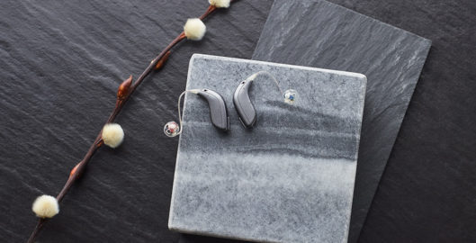 Oticon Opn S hearing aids - silver on display on slate and marble