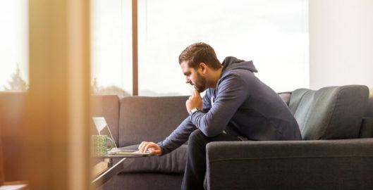 Coronavirus update - Cubex virtual hearing services - man on sofa and laptop