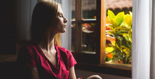 Woman in window taking a moment to breathe and destress amid covid-19